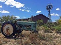 Tractor viejo oxidado en una granja con un molino de viento fotografía de archivo