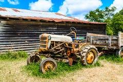 Tractor viejo por el granero de madera Imágenes de archivo libres de regalías