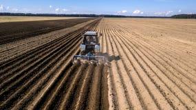 Tractor - vista a?rea de un tractor en el trabajo - que cultiva un campo en primavera con el cielo azul - maquinaria agr?cola imágenes de archivo libres de regalías