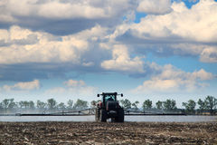Tractor watering field Stock Image