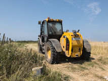 Tractor through a wheat field. In a clear sky and sunny day Royalty Free Stock Photo