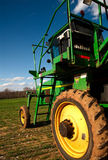 Tractor wheels. A green tractor with dirt in it's wheels on an open field stock images