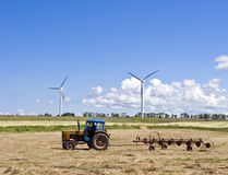 Tractor and wind turbines. A tractor working in a field, raking the hay with a simple machine, wind turbines in the background Stock Photo