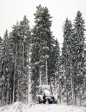 Tractor in winter forest Royalty Free Stock Photos