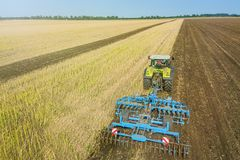Tractor at work, cultivating a field, Seedbed cultivator Aerial. View stock photos