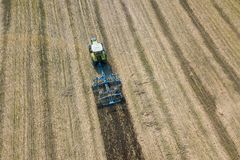Tractor at work, cultivating a field, Seedbed cultivator Aerial. View agricultural fields stock photography