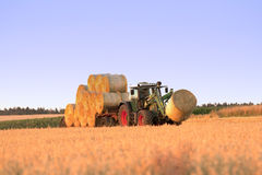 Tractor at work on field transporting haystacks Stock Photo
