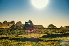 Tractor working agicultural machinery in sunny day. Working Tractor agicultural machinery on a sunny spring day at a field of grass - sunset or sunrise Stock Images