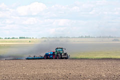 Tractor working on arable land Stock Photos
