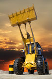 Tractor working in a career at sunset Royalty Free Stock Image