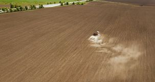 Tractor working on cultivated fields farmland and agriculture occupation top view. Aerial view of harvester tractor in a field creating an abstract background Stock Photo