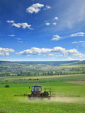 Farming tractor plowing and spraying on field vertical Royalty Free Stock Image