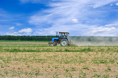 Tractor working in the field, against the blue sky.  Stock Image