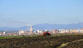 Tractor working field. In the background Power Plant Royalty Free Stock Photography