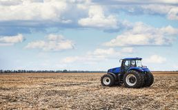 Tractor working in the field. Tractor working on the farm, a modern agricultural transport, a farmer working in the field, fertile land, tractor on cloudy sky Stock Photography