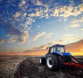 Tractor working in the field. Tractor working on the farm, a modern agricultural transport, a farmer working in the field, fertile land, tractor on a sunset Royalty Free Stock Photos