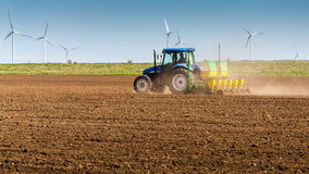 Tractor working on field with windmill turbines Stock Images