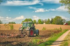 Free Tractor Working On The Farm, A Modern Agricultural Transport, A Farmer Working In The Field, Fertile Land, Tractor On A Sunset Royalty Free Stock Photography - 153569977