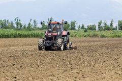 A tractor working planting wheat in the fertile farm fields of G Royalty Free Stock Image