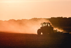 Tractor working. Silhouette of tractor working on a farm at twilight royalty free stock photos