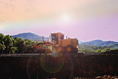 Tractor. Works in construction site over blurred mountain background sunset pastel. heavy industry and safety at work concept Stock Photo