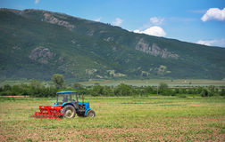 Tractor works in field. Stock Photos
