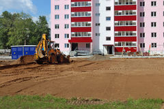 Tractor works near building on construction site at summer d Stock Photos