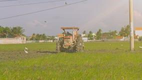 Tractorbestuurder Plows Field om Rijst door Dorp te planten stock videobeelden