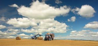 Tractoren bij oogst en mooi landschap Stock Afbeeldingen