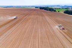 Tractoren harrownig het grote bruine gebied stock afbeeldingen