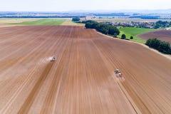 Tractoren harrownig het grote bruine gebied stock foto