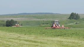 Tractores de cultivo que se mueven en el campo agrícola para cosechar la tierra Maquinaria agrícola en la cosecha del campo metrajes