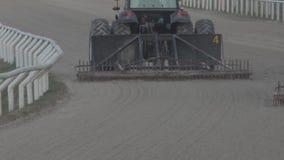 Tractores grandes que condicionan la arena de la pista almacen de metraje de vídeo