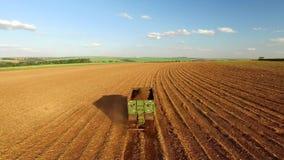 Tractores que acanalan y que abonan el suelo, preparando la tierra a la plantación de la caña de azúcar - visión aérea - día sole almacen de metraje de vídeo