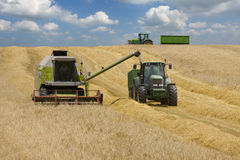 Tractors and combines in barley field Royalty Free Stock Image