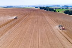 Tractors harrownig the large brown field stock images
