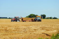 Tractors load bales of hay Royalty Free Stock Photos