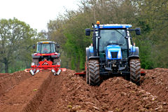 Tractors ploughing. In muddy field Royalty Free Stock Photo