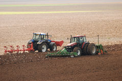 Tractors ploughing field Stock Photo