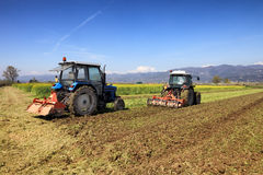 Tractors plowing a field Royalty Free Stock Photos