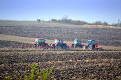 Tractors plowing hazy fall field Royalty Free Stock Photography