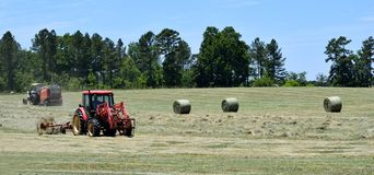 Tractors rolling bales of hay Stock Photography