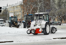 Tractors with snowplowing equipment on streets Stock Photos