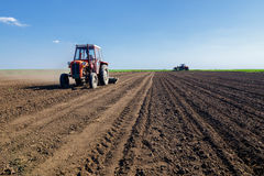 Tractors sowing on agricultural fields on beautiful sunny spring Stock Photo