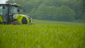Tractors sprayed with fertilizer. Tractors scatters fertilizer on the wheat field stock footage