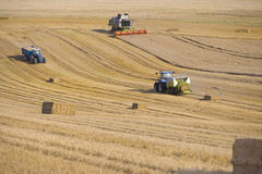 Tractors, straw balers and combine in sunny, rural field Stock Photography
