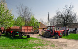 Tractors and trailers on the old fashioned farm Stock Images