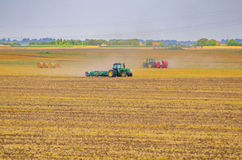 Tractors working on the agricultural field Stock Photo