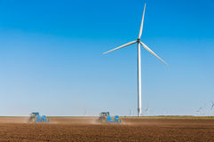 Tractors working on crop field near wind turbines Stock Photography