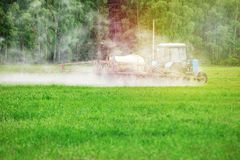 Tractror spraying pesticides, insecticide or herbicides. On the green feeld. Environmental harm concept royalty free stock photo
